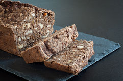 Home made rye bread. Home made rye and walnut bread cut and sliced on stone slate Royalty Free Stock Photo