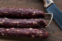 Home made smoked sausages on wooden board Stock Photo