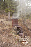 Home-made smoker. For preservation of fish and meat by fumigation in action stock photos