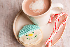 Home made snowman cookie and hot chocolate. Home made snowman cookie, candy canes and hot chocolate on a plate Stock Photos