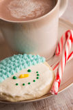 Home made snowman cookie and hot chocolate. Home made snowman cookie, candy canes and hot chocolate on a plate close up vertical Royalty Free Stock Image