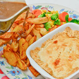 Home made Steak and Ale pie with home made chips and gravy Stock Images