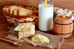 Home made sweet cookies on a burlap and basket. Milk in a glass jar with a straw. Small wooden decorative keg and spoon. Royalty Free Stock Photos