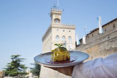 Home made tagliatelle in San Marino. Chef shows a plate of home made tagliatelle with in the background the palace of the regents of the Republic of San Marino stock photography