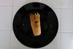 Home made tamale on a black plate set on a white tile surface. stock photos