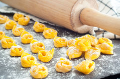 Home made tortellini. Fresh, home made Italian tortellini on a stone work top with a rolling pin and towel in the background Stock Photography