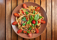 Home made vegan pasta with mushrooms, tomatoes and basil. Home made vegan pasta with mushrooms, tomatoes, basil, peppers and aubergines - served on plate at Royalty Free Stock Image