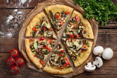 Home-made vegan pizza with tomatoes, bell peppers, mushrooms and fennel on an old wooden table. Top view.  royalty free stock photo