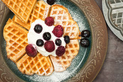 Home made waffles. Home made heart shaped waffles served with greek yogurt and frozen berries and a dusting of icing sugar. A delicious breakfast treat Stock Photography