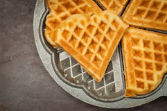 Home made waffles. Home made heart shaped waffles served in a traditional cast iron waffle pan Royalty Free Stock Images