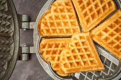 Home made waffles. Home made heart shaped waffles served in a traditional cast iron waffle pan Royalty Free Stock Photography