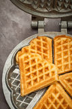 Home made waffles. Home made heart shaped waffles served in a traditional cast iron waffle pan Stock Photos