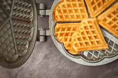 Home made waffles. Home made heart shaped waffles served in a traditional cast iron waffle pan Royalty Free Stock Photos