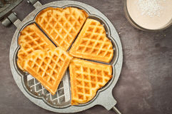 Home made waffles. Home made heart shaped waffles served in a traditional cast iron waffle pan with a healthy peanut butter banana smoothie milkshake Stock Images