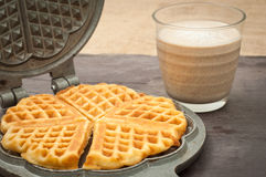 Home made waffles. Home made heart shaped waffles served in a traditional cast iron waffle pan with a healthy peanut butter banana smoothie milkshake Royalty Free Stock Image