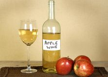 Home made wine. Bottle and glass of home made apple wine with apples royalty free stock photography