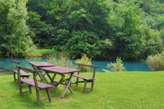 Home made wooden bench and table next to very scenic and green river bank. Eastern Serbia, `Krupajsko Vrelo`, near Despotovac city stock images