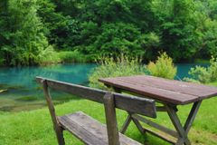 Home made wooden bench and table next to very scenic and green river bank. Eastern Serbia, `Krupajsko Vrelo`, near Despotovac city royalty free stock photography