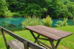 Home made wooden bench and table next to very scenic and green river bank. Eastern Serbia, `Krupajsko Vrelo`, near Despotovac city royalty free stock images