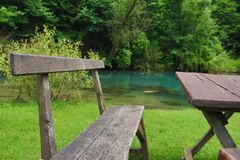 Home made wooden bench and table next to very scenic and green river bank. Eastern Serbia, `Krupajsko Vrelo`, near Despotovac city stock image