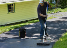Home maintenance. Do it yourself  driveway  resealing. Homeowner doing home maintenance spreads blacktop sealant  over driveway Royalty Free Stock Photos
