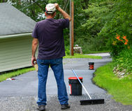Home maintenance. Do it yourself  driveway  resealing. Homeowner looks over a the portion of driveway that has been resealed Stock Photo