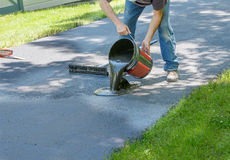 Home maintenance. Do it yourself  driveway  resealing. Man doing home maintenance pours blacktop sealer over driveway before spreading it Stock Images