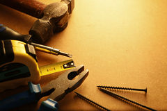 Home maintenance tool kit. In a sepia toned image arranged in a semi circle on the border with a hammer, pliers, screwdriver, tape measure and nails surrounding Stock Photography