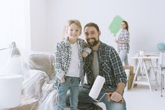 Family renovating their new apartment. Home makeover, decoration and painting: a father is posing with his son and holding a paint roller, his wife is painting Royalty Free Stock Images