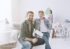 Family renovating their new apartment. Home makeover, decoration and painting: a father is posing with his son and holding a paint roller, his wife is painting Royalty Free Stock Image