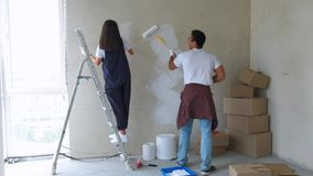 Home makeover and renovation: young happy couple painting their new house interiors using paint rollers stock video footage