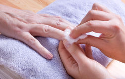 Home Manicure. Older senior woman with arthritic hands receiving home spa treatment / manicure Royalty Free Stock Images