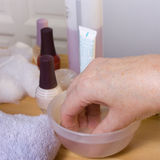 Home Manicure. Older senior woman with arthritic hands receiving home spa treatment / manicure Stock Images