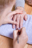 Home Manicure. Older senior woman with arthritic hands receiving home spa treatment / manicure Royalty Free Stock Photos