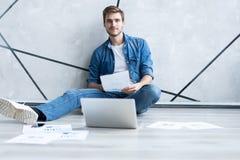 home manworking Stilig ung man som sitter på golv- och undersökadokumentet medan lägga för bärbar dator och för dokument royaltyfria bilder