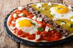 Home Mexican food: huevos divorciados with Frijoles refritos, two sauces roja and verde and cheese Queso Fresco on tortilla macro royalty free stock photos