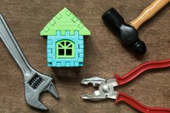 Home model object with toy equipment tool on wood background. Concept for home repair or fix royalty free stock images