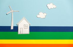 Home model and windmill on colorful background Stock Photos