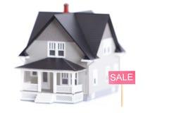 Home modell med försäljningstecknet som isoleras Arkivfoton