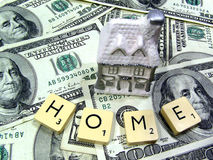 Home money. Home made of porcelain on background made of US dollar bills (hundreds) and scrabble tiles Stock Images