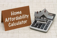 Home Mortgage Affordability Calculator, A gray house, brown card. And calculator on stone background with text   Home Affordability Calculator Royalty Free Stock Image