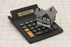 Home Mortgage Interest Rates, A gray house and calculator on sto Royalty Free Stock Photos