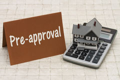 Home Mortgage Pre-approval, A gray house, brown card and calculator on stone background. With text Pre-approval royalty free stock image