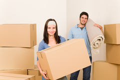 Home moving young couple boxes and carpet royalty free stock image