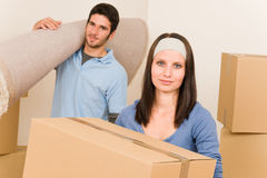 Home moving young couple boxes and carpet Stock Images