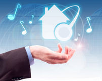 HOME MUSIC and Musical Note. Hand, digital button HOME MUSIC and Musical Note on background map of world royalty free stock photography