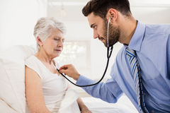 Home nurse listening to chest of patient with stethoscope Stock Photos