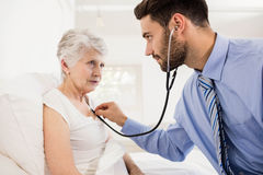 Home nurse listening to chest of patient with stethoscope Stock Image