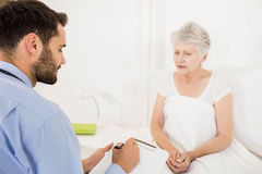 Home nurse listening to elderly woman and writing on clipboard Stock Images