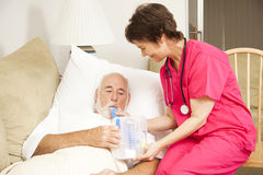 Home Nursing - Breathing Exercise. Home health nurse helps a senior patient with his respiratory therapy Stock Images